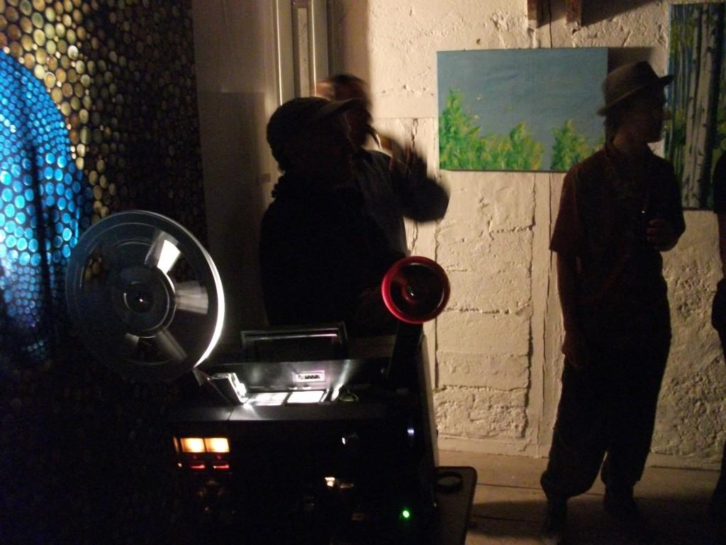 Der Elmo GS1200 250W während der Projektion zwischen Ausstellungsgästen und Bildern der beiden Künster.